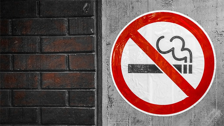 The figure shows a smoking is not allowed sign on a concrete wall.