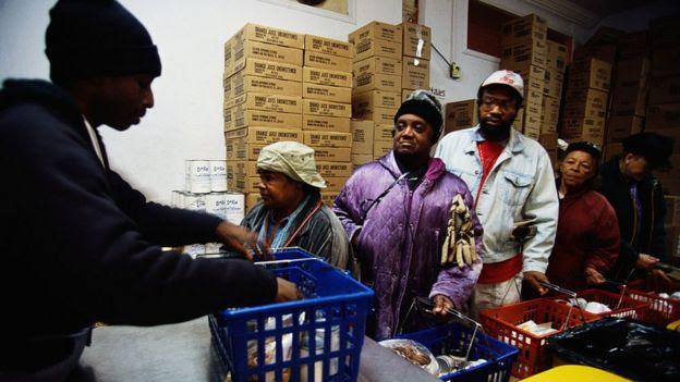 Pessosas negras em fila para receber alimentos
