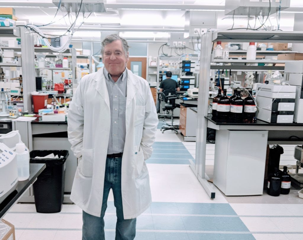 A man in a white lab coat, Dr. Thomas Meek, stands in a laboratory setting
