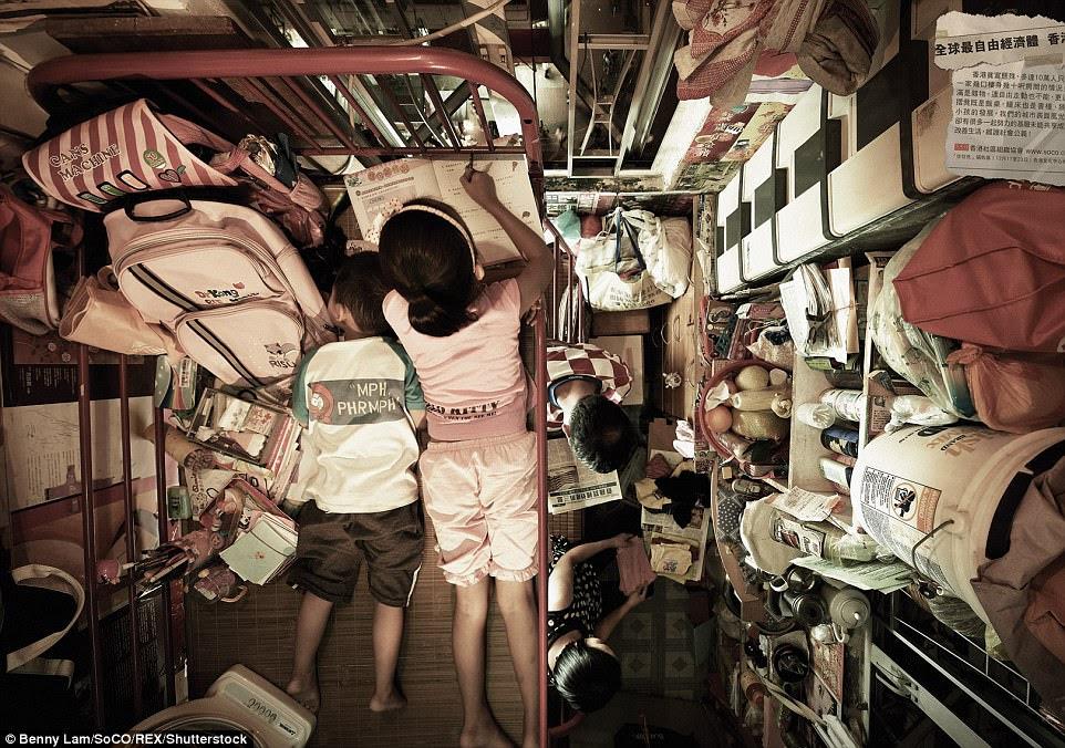 Trẻ em nằm trên giường trong khi hẹp, bên dưới, nhiều người đang nhồi nhét vào không gian nhỏ