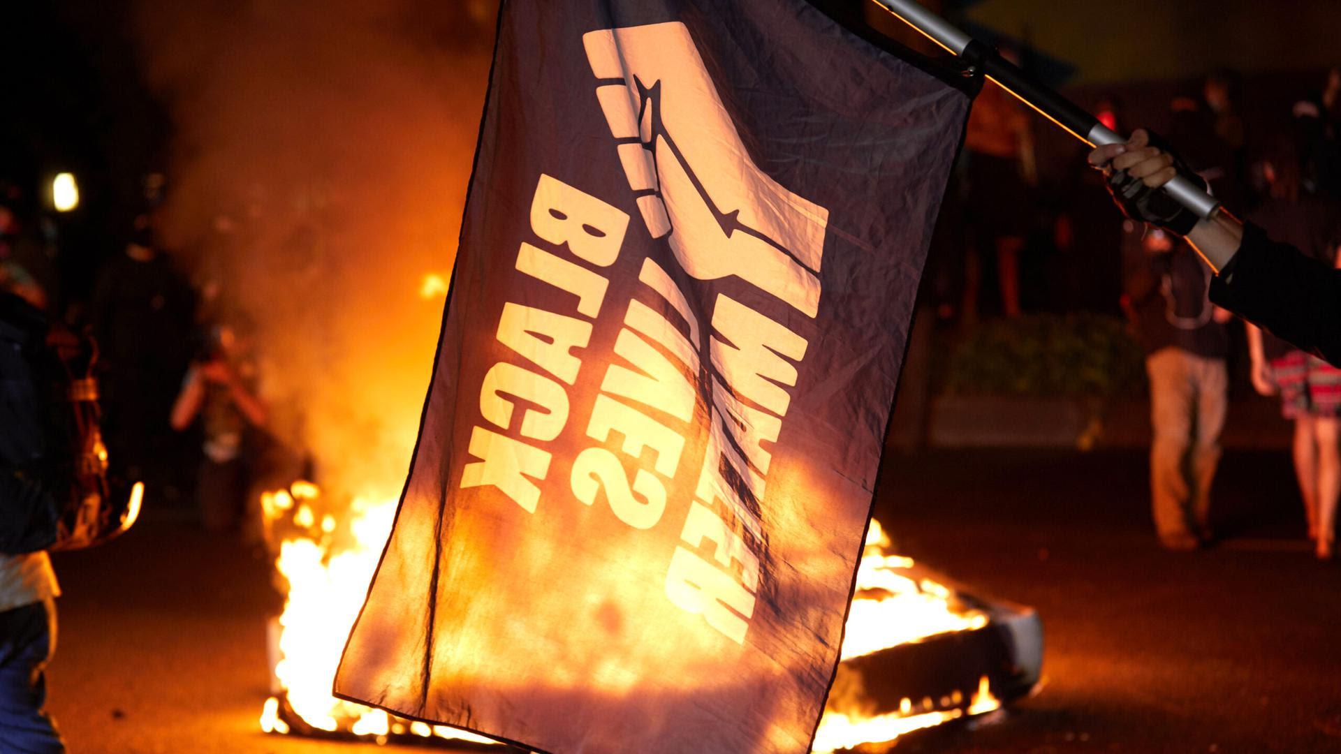 A Black Lives Matter flag flying in front of burning wreckage