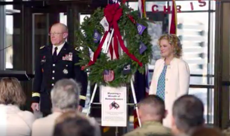 State Superintendent Jillian Balow stands beside a wreath with Wyoming Adjutant General Luke Reiner during a ceremony in Cheyenne.