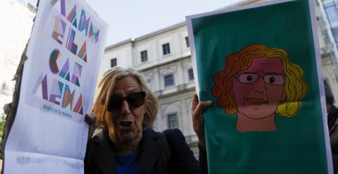 Manuela Carmena sostiene dos carteles sobre su candidatura, durante la campaña electoral. REUTERS/Sergio Perez