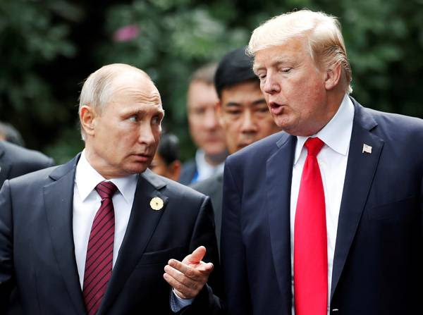 President Trump and Russian President Vladimir Putin talk during a photo session at the APEC Summit in Danang, Vietnam, in 2017. (Jorge Silva/Reuters)</p>