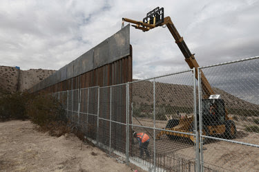 Workers raising a taller fence along the United States-Mexico border in November. President Trump wants to erect a border wall, paid for with Mexican money.