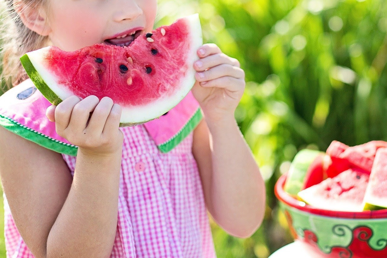 This shows a little girl eating fruit