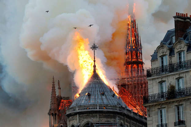 Slide 27 of 31: Smoke and flames rise during a fire at the landmark Notre-Dame Cathedral in central Paris on April 15, 2019, potentially involving renovation works being carried out at the site, the fire service said. (Photo by FRANCOIS GUILLOT / AFP)        (Photo credit should read FRANCOIS GUILLOT/AFP/Getty Images)
