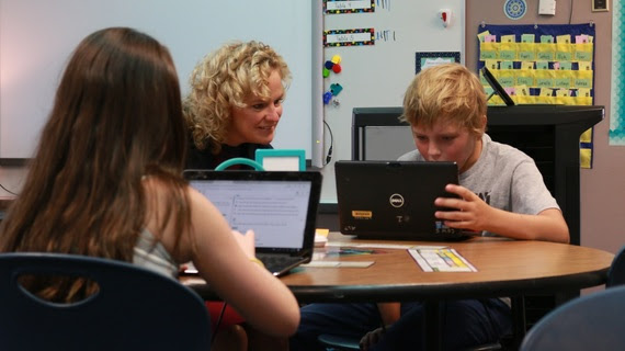 State Superintendent Jillian Balow smiles while sitting next to a fifth-grade student as he concentrates on a laptop which hosts the training test for Wyoming's new statewide assessment.