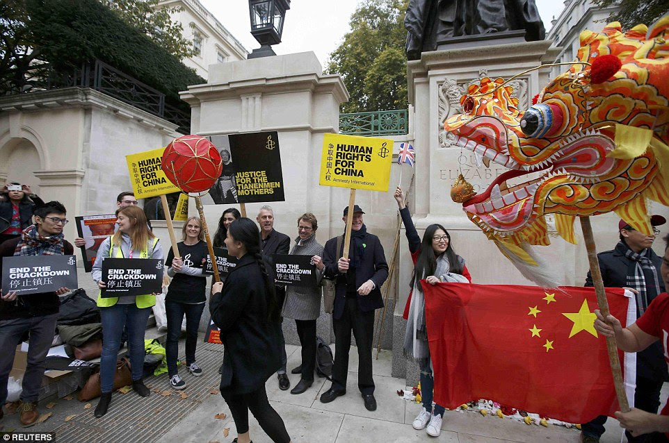 Stand-off: Flag-waving pro-China supporters parade past Amnesty International protesters with a traditional dragon (head pictured)