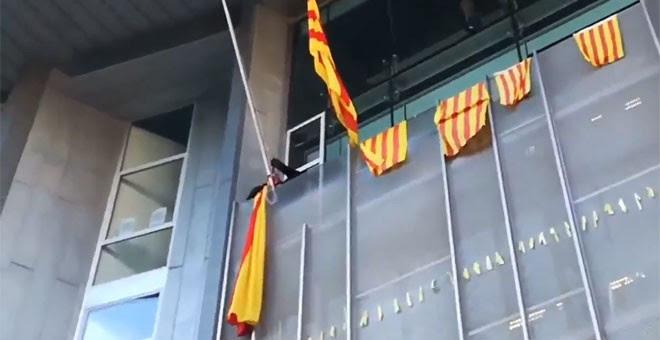 Momento en el que un grupo de los CDR retira la bandera española en la Delegación de la Generalitat en Girona