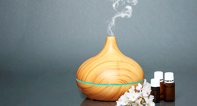 Wood essential oil diffuser and essential oil bottles on a grey background