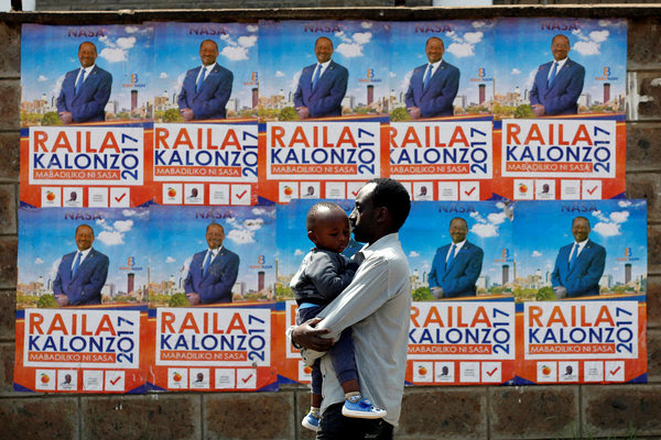A man carries a child in front of campaign posters showing Kenyan opposition leader Raila Odinga on Aug.6. (Baz Ratner/Reuters)</p>