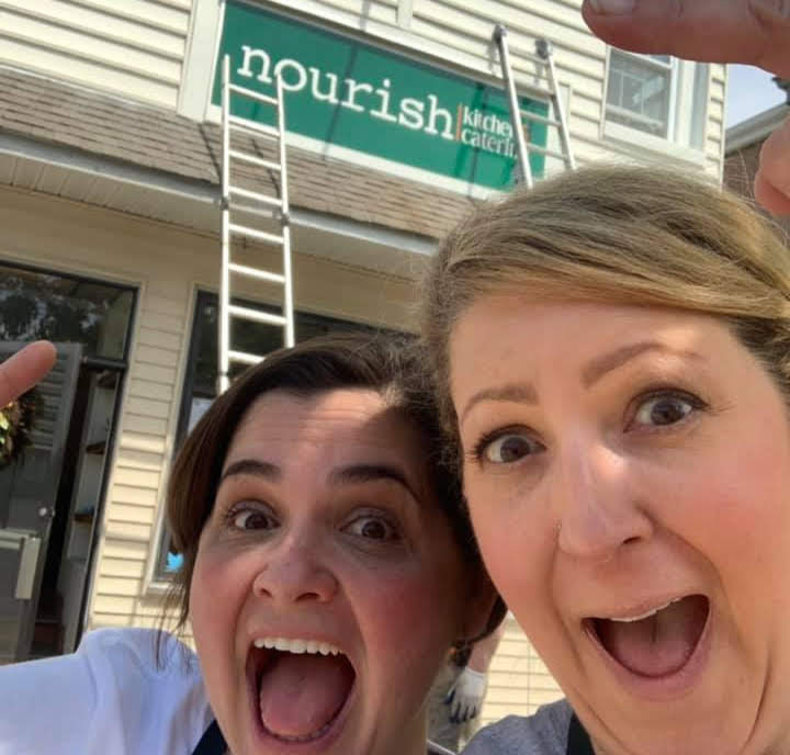 Owners of Nourish in front of sign