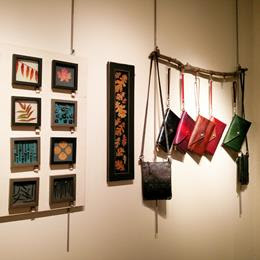 Photo of small artworks of resin and encased items, and also hand-made leather purses and clutches