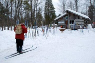 A man in a red jacking skiing towards a ski rental cottage