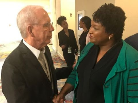 From left to right, Tony Coelho and Stacey Abrams, shaking hands and looking at each other in conversation.