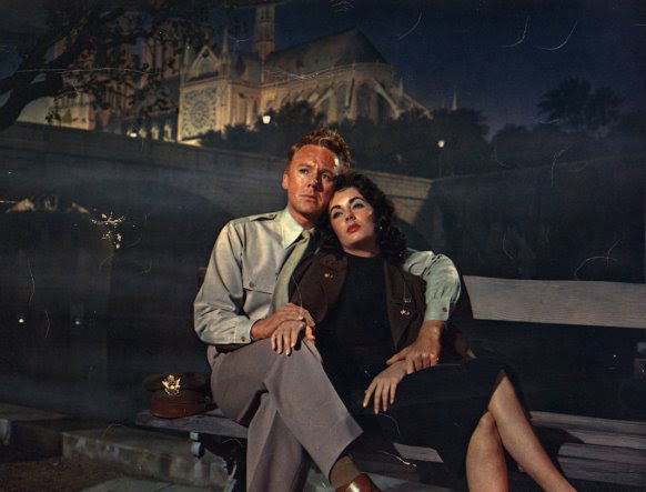 ctors Van Johnson and Elizabeth Taylor sitting on bench with cath