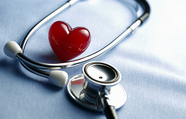 A plastic heart with a stethoscope around it.