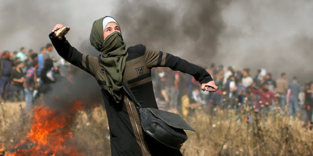Girl hurls stones during clashes with Israeli troops at a protest where Palestinians demand the right to return to their homeland, at the Israel-Gaza border, east of Gaza City