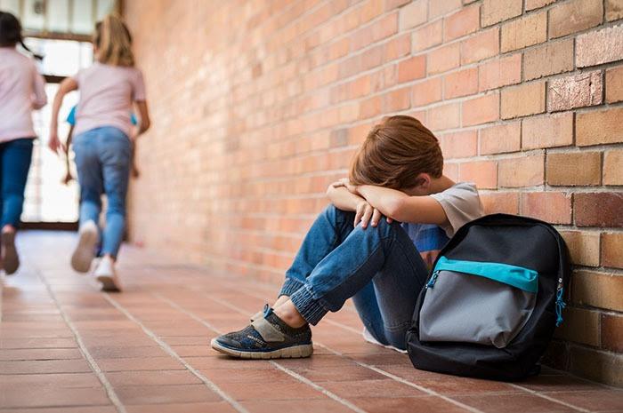 A sad boy in the school hallway