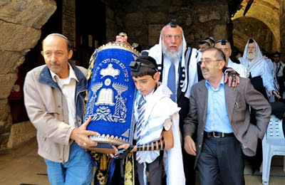 A Jewish father and son at the                 Western (Wailing) Wall in Jerusalem share the burden of                 carrying the heavy Torah scroll. (Photo by Reinhardt                 Konig)