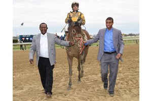 Uriah St. Lewis (left) and his son Uriah St. Lewis Jr. lead Discreet Lover to the winner's circle after his victory in the Excelsior Stakes at Aqueduct